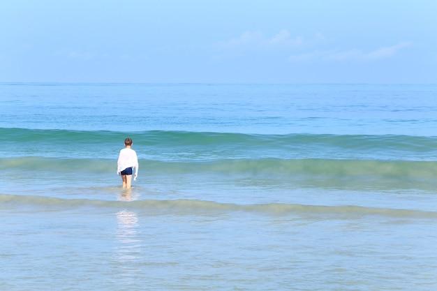 Chemise blanche de garçon de race blanche s'amusant avec une grande vague blanche sur un ciel bleu océan vert