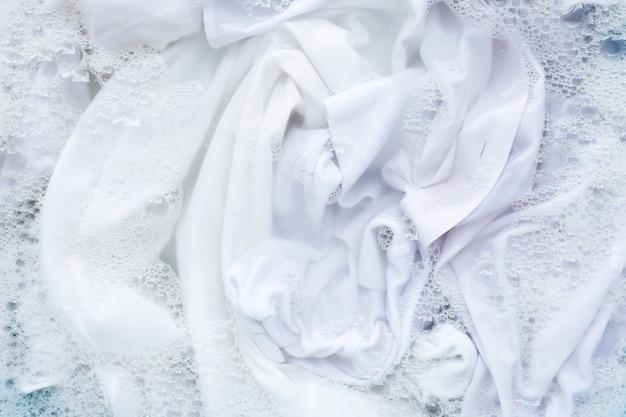 Chemise blanche imbibée de dissolution en poudre de détergent en poudre. concept de blanchisserie