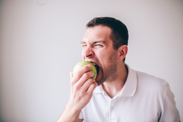Chemise blanche jeune manin isolé sur fond. guy mordre un morceau de pomme verte fraîche savoureuse. délicieux fruits délicieux.