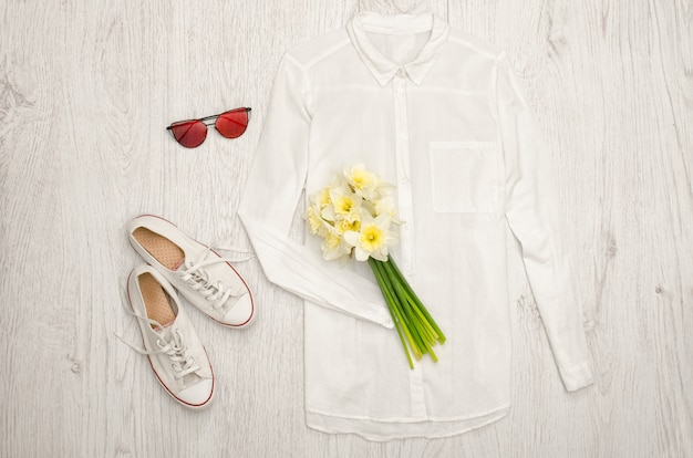 Chemise blanche, lunettes, baskets et un bouquet de jonquilles.