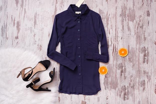 Chemise bleue, chaussures noires, fourrure blanche et agrumes