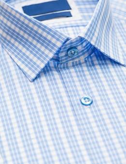 Chemise bleue avec motif à carreaux et mettant l'accent sur le col et le bouton, gros plan