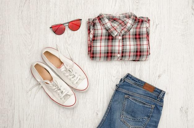 Chemise à carreaux rouge et blanc, lunettes, baskets et jeans.