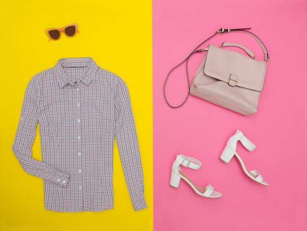 Chemise dans une petite cage, sac à main, chaussures blanches et lunettes. fond rose-jaune vif