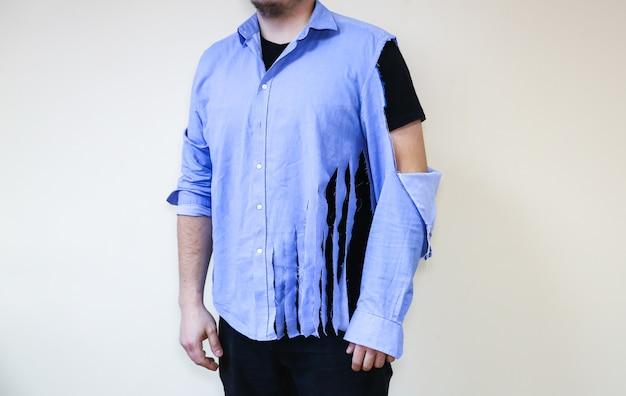Chemise déchirée. homme vêtu de vieux vêtements qui ont besoin d'être réparés et cousus.