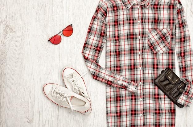 Chemise femme à carreaux, sac à main noir, baskets blanches, lunettes. concept à la mode, mur en bois