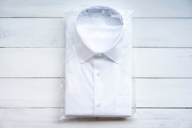 Chemise formelle blanche décontractée pliante dans l'emballage en plastique blanc