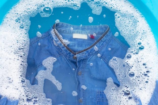Chemise en jean imbibée de poudre, détergent, eau, dissolution, linge à laver.