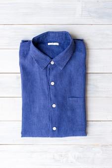 Chemise en lin bleu plié sur fond de table en bois blanc.