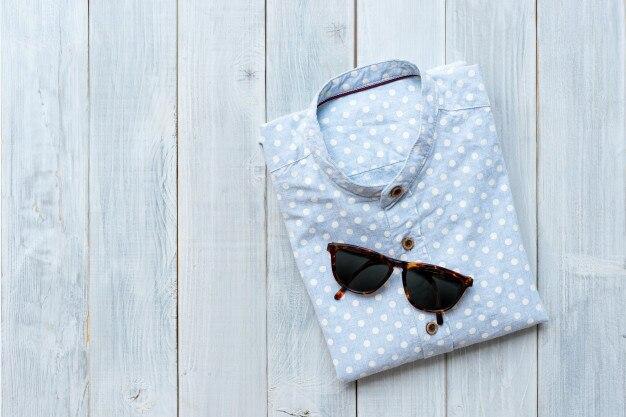 Chemise en lin polkadot bleu clair pliée avec des lunettes de soleil sur fond de table en bois blanc.