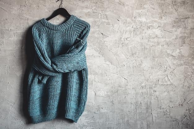 Chemise à manches longues chaude bleue sur cintre noir accrocher sur fond gris
