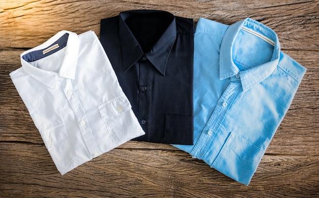 Chemise noire, chemise blanche et chemise de jeans sur fond en bois