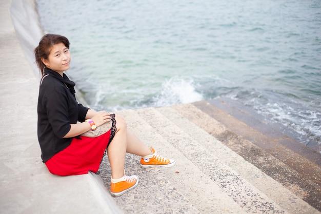 Chemise noire des femmes asiatiques. assis sur le trottoir.
