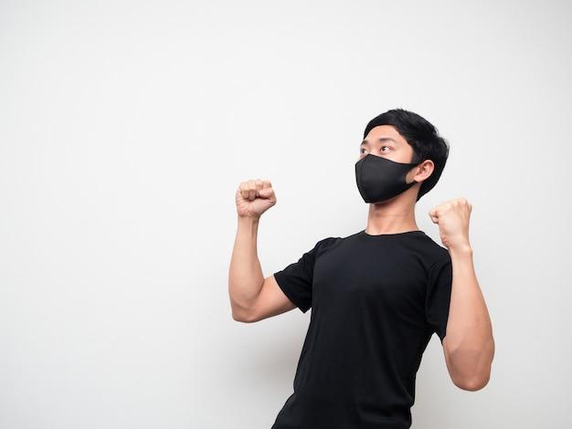 Chemise noire d'homme asiatique avec le double poing de masque et levez les yeux se sentent heureux sur le fond blanc d'isolat
