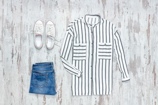 Chemise à rayures blanches et bleues, baskets et jeans blancs