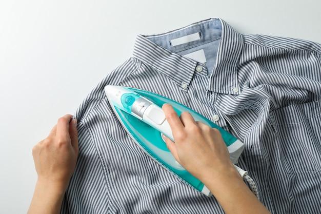 Chemise de repassage de jeune femme sur blanc, vue de dessus