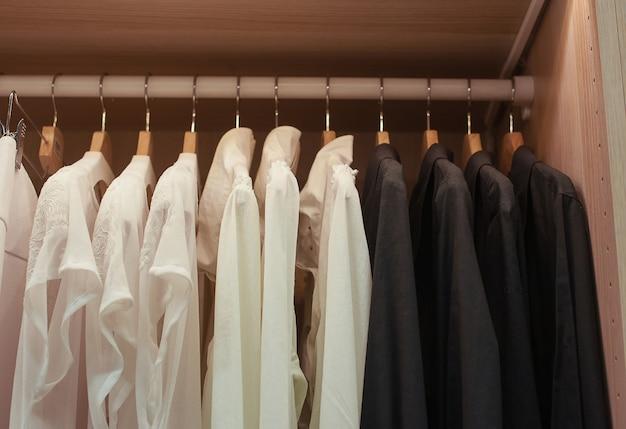 Chemises blanches et noires sur trempele dans le placard