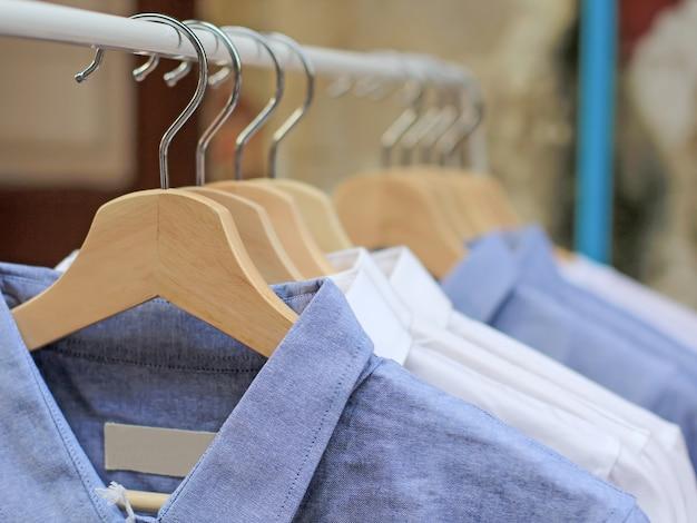 Chemises bleues et blanches suspendus sur une étagère dans la garde-robe