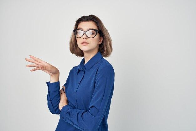 Chemises bleues de femme avec la mode de lunettes posant le fond clair