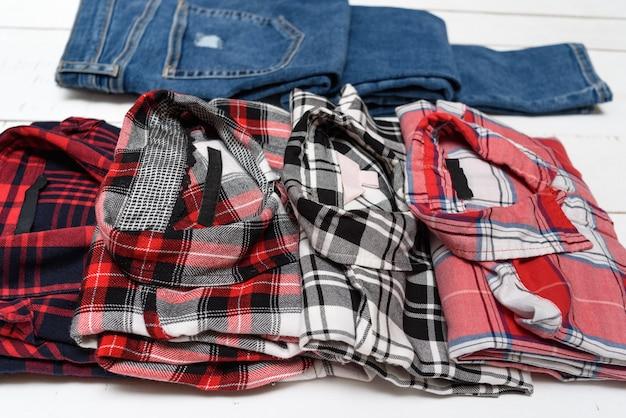 Chemises à carreaux et jeans bleu sur un bois blanc