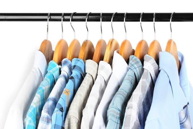 Chemises avec des liens sur des cintres en bois sur fond clair