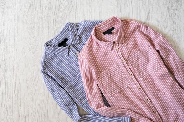 Chemises à rayures roses et bleues sur fond en bois. concept à la mode