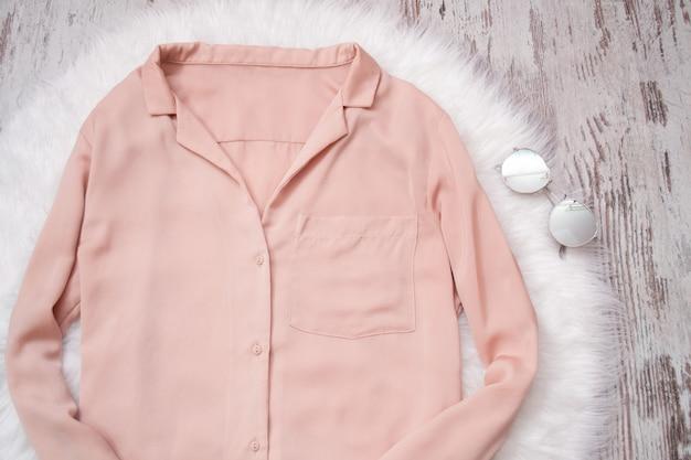Chemisier rose pâle sur une lunette de fourrure blanche. à la mode, vue de dessus