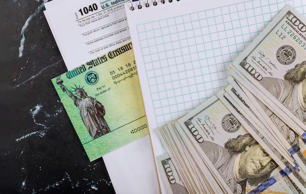 Chèque de déclaration de revenus et dollar en espèces monnaie des états-unis 1040 formulaire d'impôt américain
