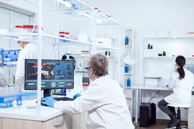 Chercheur âgé travaillant à trouver un remède pendant la pandémie mondiale. scientifique principal dans un laboratoire pharmaceutique effectuant des recherches génétiques portant une blouse de laboratoire avec une équipe en arrière-plan.