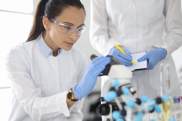 Chercheur et collègue mènent des recherches en laboratoire sous microscope