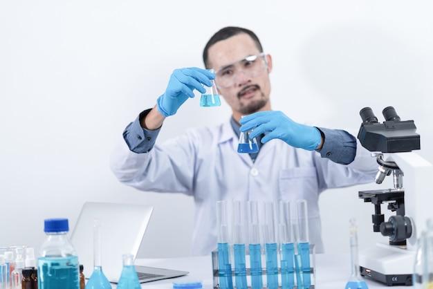 Chercheur en laboratoire etudier avec des produits chimiques et des microscopes