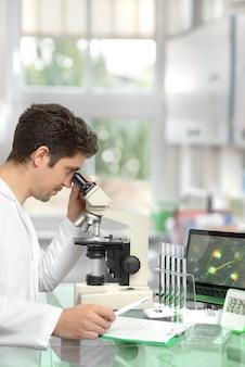 Chercheur masculin avec microscope dans un centre de recherche moderne