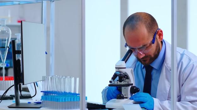 Chercheur médical effectuant le développement de vaccins sous microscope numérique dans un laboratoire de sciences appliquées biologiques. ingénieur de laboratoire caucasien en blouse blanche travaillant sur un traitement médical