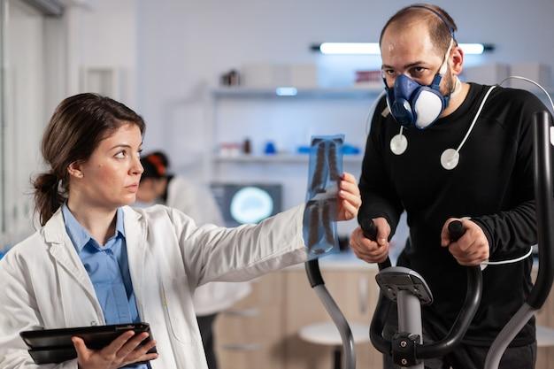 Chercheur médical examinant l'évolution de l'état de santé de l'athlète, regardant les rayons x, tandis qu'un homme avec un masque court sur un vélo elliptique surveillant son endurance. le moniteur montre la lecture ecg du sportif.