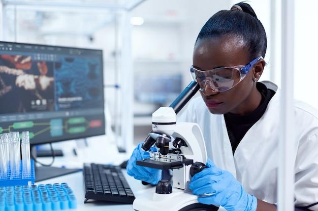 Chercheur médical d'origine africaine utilisant un microscope pour enquêter et évaluer l'échantillon. scientifique noir de la santé dans un laboratoire de biochimie portant un équipement stérile.