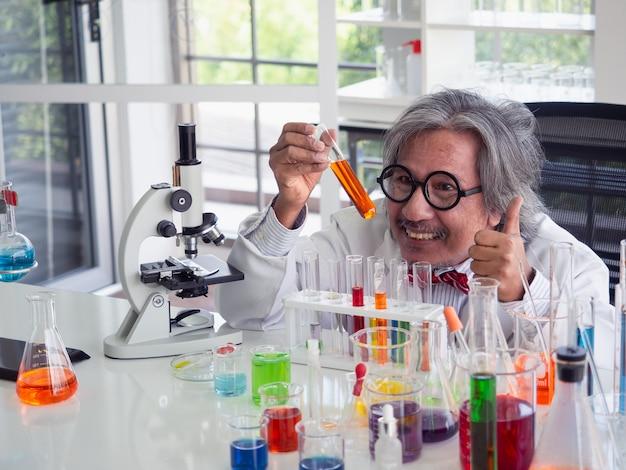 Chercheur scientifique en asie tenant un tube à essai de solution claire dans un laboratoire