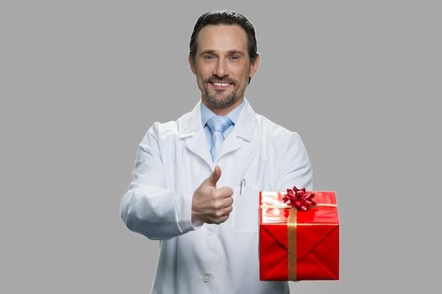Chercheur scientifique montrant la boîte-cadeau et le pouce vers le haut. concept de célébration de vacances.