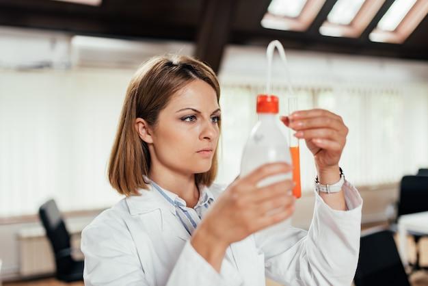 Chercheur scientifique tenant une eau dans des bouteilles en plastique avec une pompe. fermer.