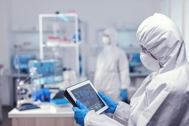 Chercheur en soins de santé analysant le virus sur tablet pc pendant la pandémie mondiale sur tablet pc. équipe de scientifiques menant le développement de vaccins à l'aide d'une technologie de pointe pour la recherche de traitements contre c
