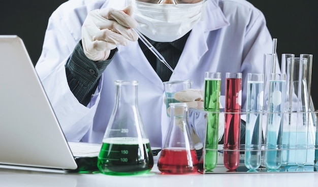 Chercheur avec tubes à essai chimiques de laboratoire en verre avec liquide
