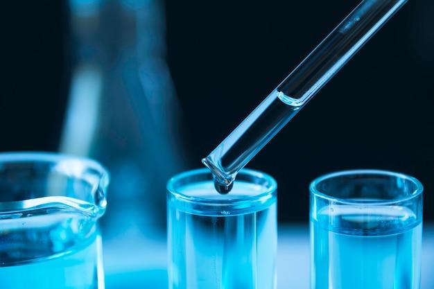 Chercheur avec des tubes à essai chimiques de laboratoire en verre