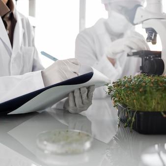 Chercheurs avec presse-papiers dans le laboratoire de biotechnologie