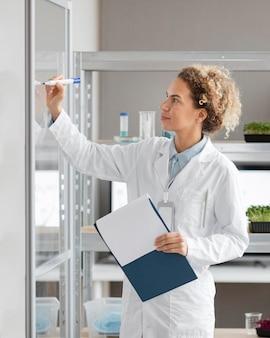 Chercheuse avec presse-papiers dans le laboratoire de biotechnologie
