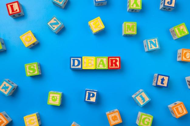 Chère. blocs d'alphabet coloré en bois sur bleu