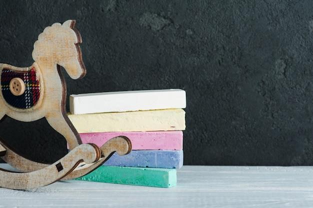 Cheval à bascule vintage à côté du tableau noir