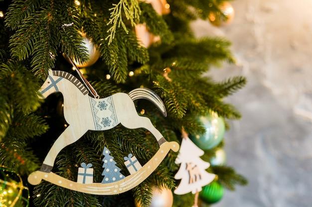 Cheval en bois jouet de noël sur une branche de sapin, décoration scandinave