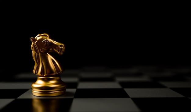Cheval d'échecs d'or debout seul sur l'échiquier