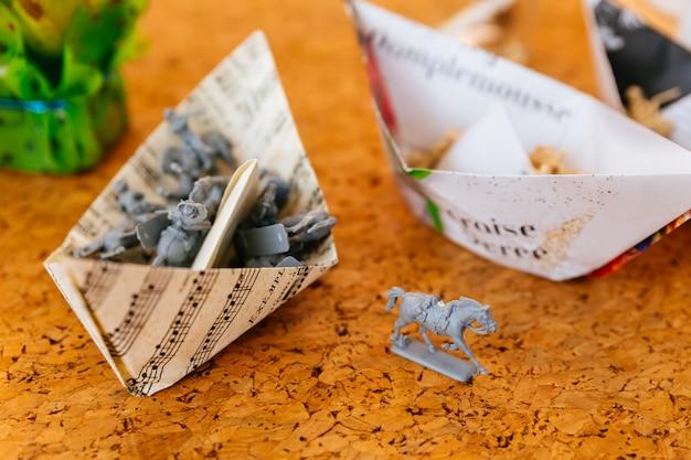 Cheval gris miniature avec des modèles miniatures dans des bateaux pliants en papier.