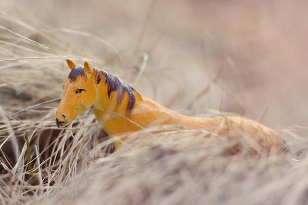 Cheval jouet dans la nature photographié comme réel parmi l'herbe sèche comme des meules de foin