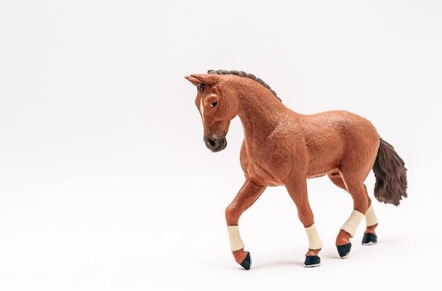 Cheval jouet en plastique réaliste, isoler sur une surface blanche